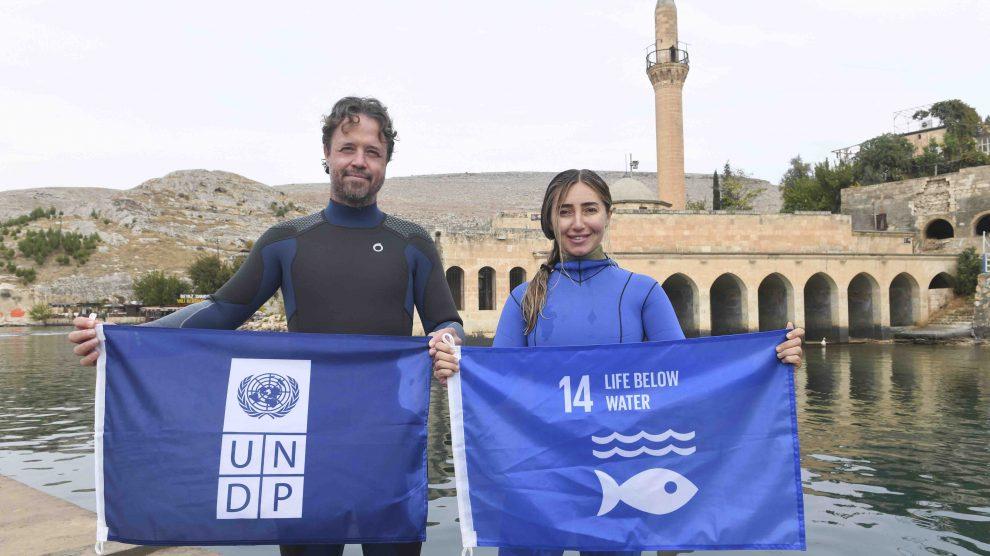 """UNDP Türkiye, Suriye krizinin çevresel etkilerine yönelik olarak atık ve atık yönetimi konularında Kilis ve Şanlıurfa-Haliliye belediyeleri ile birlikte yürüttüğü proje kapsamında Dünya serbest dalış rekortmeni ve UNDP 'Sudaki Yaşam Savunucusu' Şahika Ercümen ile Halfeti'de Sıfır Atık Dalışı gerçekleştirdi. Birleşmiş Milletler Kalkınma Programı (UNDP) Türkiye Ülke Ofisi, rekortmen sporcu Şahika Ercümen ve basın mensuplarının katılımıyla Şanlıurfa'da sürdürülebilir kalkınma ve sosyo-ekonomik gelişmeye yönelik çeşitli UNDP projelerini ziyaret etti. Şanlıurfa'nın Haliliye ilçesi ve Kilis'te yürütülen """"Sıfır Atık"""" projesi kapsamında gerçekleşen ziyaretler sonrası Ercümen, Halfeti'de, UNDP Türkiye Mukim Temsilcisi Claudio Tomasi ile birlikte atık, kirlilik ve sürdürülebilirlik konularına dikkat çekmek için bir dalış gerçekleştirdi. Halfeti'de gerçekleştirilen """"Sıfır Atık Dalışı"""" öncesinde düzenlenen etkinlik ve basın toplantısına; Şanlıurfa Vali Yardımcısı Metin Esen, Halfeti Kaymakamı Selami Korkutata, Halfeti Belediye Başkanı Şeref Albayrak, Haliliye Belediye Başkanı Mehmet Canpolat ve Kilis Belediye Başkanı Servet Ramazan'ın yanı sıra, UNDP Türkiye Mukim Temsilcisi Claudio Tomasi ve UNDP Türkiye'nin """"Sudaki Yaşam Savunucusu"""" Şahika Ercümen de katılarak sürdürülebilir kalkınma gündemi, çevre kirliliği, atık ve UNDP'nin Suriye krizinin çevresel etkilerine yönelik projeleri konularında açıklamalarda bulundu. """"Ev Sahibi Topluluklar İçin Etkin Kentsel Atık Yönetimi, Faz 2: Katılımcı Atık Yönetimi Aracılığı İle Sosyal Uyumun Güçlendirilmesi"""" projesi kapsamında gerçekleştirilen etkinlik, Kilis ve Haliliye'nin atık sorununa yönelik sürdürülebilir çözümlere ve sosyal uyum konusuna dikkat çekmeyi amaçladı. Sıfır Atık Projesi önemli çünkü """"Gezegenimiz, aslında bizim evimiz. Ve başka bir evimiz yok"""" Etkinliğin açılış konuşmasını gerçekleştiren UNDP Türkiye Mukim Temsilcisi Claudio Tomasi, """"Nüfus hareketleri, göç, artan kirlilik, çevresel kaygılar ve iklim değişikliği giderek daha"""